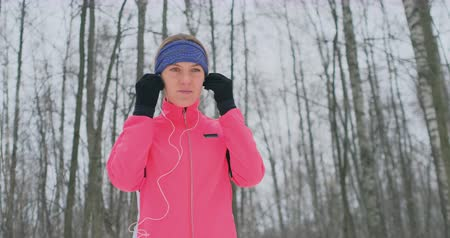 cadarço : The woman before the morning winter jog inserts headphones in the ears and is preparing to run through the natural Park in slow motion. Listening to music while running. Learn foreign languages