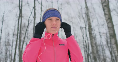 cipőfűző : The woman before the morning winter jog inserts headphones in the ears and is preparing to run through the natural Park in slow motion. Stock mozgókép