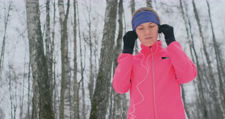 cipőfűző : A young girl on the morning jog holds in her hands a smartphone picks a music track for training. Winter run. Use modern gadgets and training applications Stock mozgókép