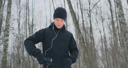 A young man in a black hammer in the winter is preparing to jog in the park includes an application for running and runs with a voice assistant through the forest doing business and leading a healthy lifestyle.