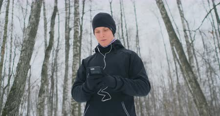 trigger : A young man in a black trigger in the winter is preparing to jog in the park includes running music on a smartphone and runs with a voice assistant through the forest doing business and leading a healthy lifestyle
