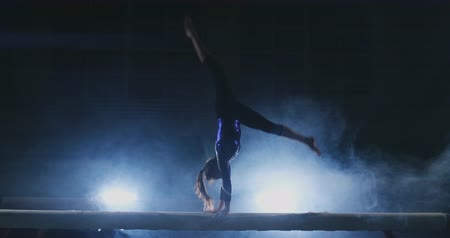 akrobata : The girl performs a trick on a log in backlight and slow motion in sports gymnastic clothing. Smoke and blue. Jump and spin on the balance beam Stock mozgókép