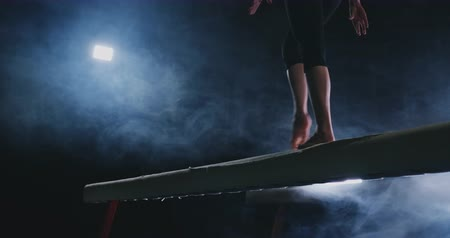 гимнаст : Close-up of the foot of a professional gymnast girl jumping in slow motion in the smoke on a balance beam. Womens gymnastics. Grace and a healthy lifestyle
