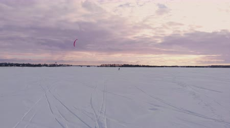 padák : A male athlete in sports outfit is doing snow kiting on beautiful winter landscape