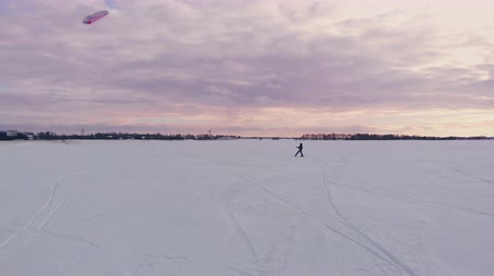 kiting : Kite surfing on a frozen lake in winter at sunset Stock Footage