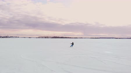 bezmotorové létání : A man is skiing in the snow in a field at sunset. His parachute pulls. Kite surfing in the snow..