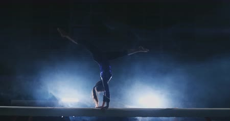 handstand : The girl is a professional athlete performs gymnastic acrobatic trick on a beam in backlight and slow motion in sports gymnastic clothing. Smoke and blue. Jump and spin on the balance beam Stock Footage