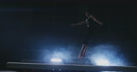 гимнаст : The girl performs a trick on a log in backlight and slow motion in sports gymnastic clothing. Smoke and blue. Jump and spin on the balance beam Стоковые видеозаписи