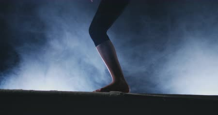 гимнаст : Legs Professional girl gymnasts jump in slow motion in the smoke on the balance beam. Womens Artistic Gymnastics