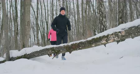 сильный : A man and a woman run in the park in winter and jump over a fallen tree. Step over the obstacle Стоковые видеозаписи