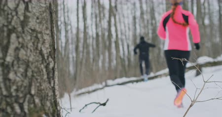 overcome : Positive beautiful young healthy couple running with sportswear through the forest in the sunny winter morning. Jump over the tree, overcome the difficulties of the path. step over an obstacle Stock Footage