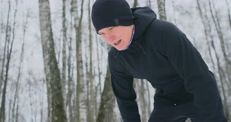 спринт : A young man on a morning jog in the winter forest was tired and stopped to rest and ran on. He recovered his strength and overcame fatigue and continued to run. Perseverance and overcoming weakness. Striving forward. Slow motion. Healthy lifestyle
