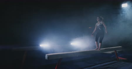 salto ostacoli : The girl performs a trick on a log in backlight and slow motion in sports gymnastic clothing. Smoke and blue. Jump and spin on the balance beam Filmati Stock