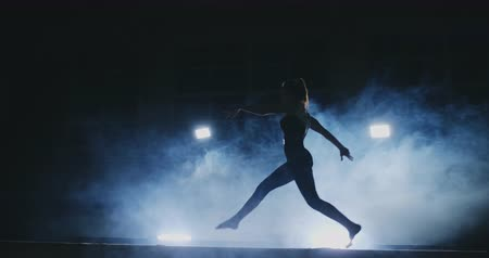 špičatý : The girl is a professional athlete performs gymnastic acrobatic trick on a beam in backlight and slow motion in sports gymnastic clothing. Smoke and blue. Jump and spin on the balance beam Dostupné videozáznamy