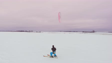 kite boarding : Kitesurfing in the winter on snowboard or ski. Skating on the ice in the wind. Beautiful colored sails.