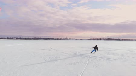 kite boarding : 4K aerial winter extreme sport snow kiting competition race with different colorful snow-kites, ski, snowboarders over the ice lake in front of city at blizzard and snow weather from drone Stock Footage