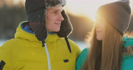 air kiss : In the winter forest at sunset loving couple skiing and look around at the beauty of nature and attractions in slow motion. Stock Footage