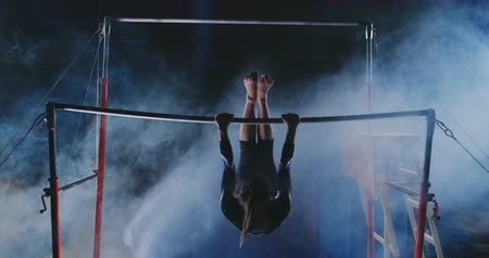 dips : Competitions in gymnastics. A woman walks to the crossbar and performs dips flip-flops in slow motion on a dark background in backlight. Slow motion.