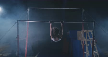 desigual : Competitions in gymnastics. A woman walks to the crossbar and performs dips flip-flops in slow motion on a dark background in backlight. Slow motion.