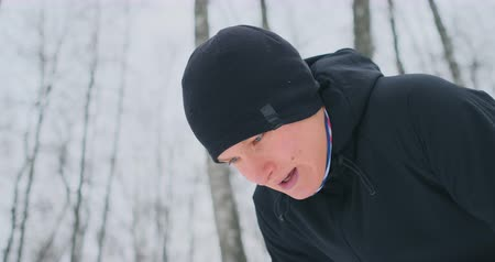 pauza : A young man on a morning jog in the winter forest was tired and stopped to catch his breath. He recovered his strength and overcame fatigue and continued to run. Perseverance and overcoming weakness. Push forward