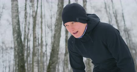 pauza : A young man on a morning jog in the winter forest was tired and stopped to rest and ran on. He recovered his strength and overcame fatigue and continued to run. Perseverance and overcoming weakness. Striving forward. Slow motion. Healthy lifestyle