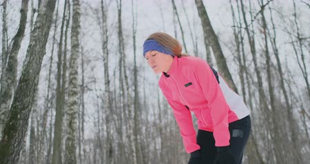 exaustão : A young woman on a morning jog in the winter forest was tired and stopped to rest and ran on. He recovered his strength and overcame fatigue and continued to run. Perseverance and overcoming weakness. Striving forward. Slow motion. Healthy lifestyle Vídeos