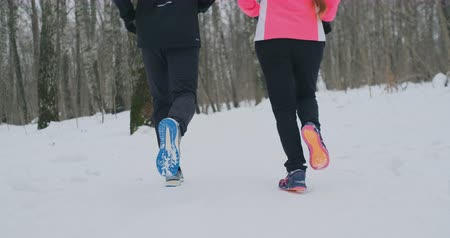 sporty zimowe : Close-up of the feet of two runners in sneakers running in the winter in the park. The married couple goes in for sports. Wideo