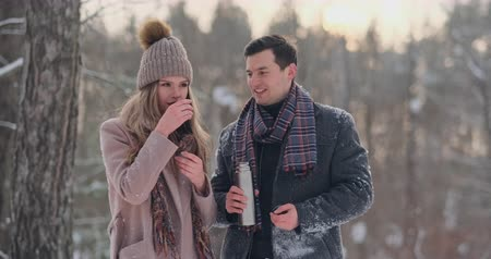 racconto : Beautiful and stylish couple man and woman hipsters in a coat and scarf drink tea from a thermos in the winter forest after a walk. Love story Filmati Stock