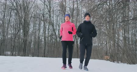 winter sport : Young man and woman on a morning run in the winter forest. A woman in a loose jacket a man in a black jacket is running through a winter park. Healthy lifestyle happy family. Stockvideo