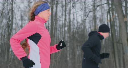 sporty zimowe : Young man and woman on a morning run in the winter forest. A woman in a loose jacket a man in a black jacket is running through a winter park. Healthy lifestyle happy family. Wideo