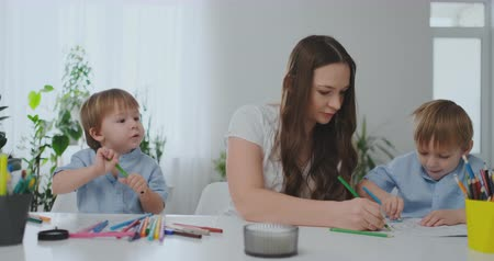 alta calidad : A young mother with two children sitting at a white table draws colored pencils on paper helping to do homework
