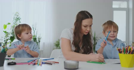 alta calidad : A family of two children and a young mother sitting at the table draws on paper with colored pencils. Development of creativity in children. white clean interior