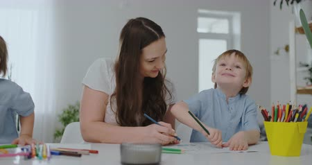alta calidad : A young mother with two children sitting at a white table draws colored pencils on paper in slow motion Archivo de Video