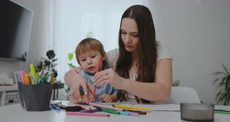 gramotnost : Sitting at the table in the living room, a young mother teaches her son to hold a pencil and teaches to draw Dostupné videozáznamy
