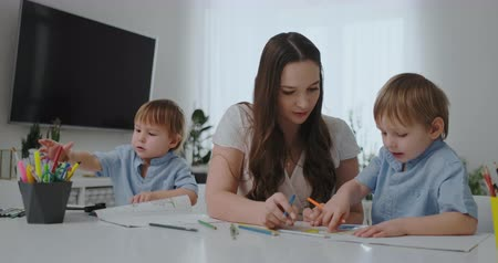 gramotnost : A young mother with two children sitting at a white table draws colored pencils on paper in slow motion Dostupné videozáznamy