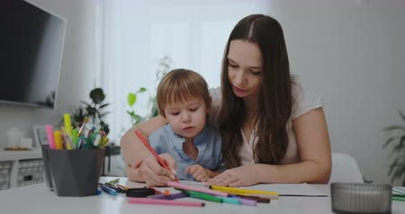 alfabetização : A family of two children and a young mother sitting at the table draws on paper with colored pencils. Development of creativity in children. Vídeos