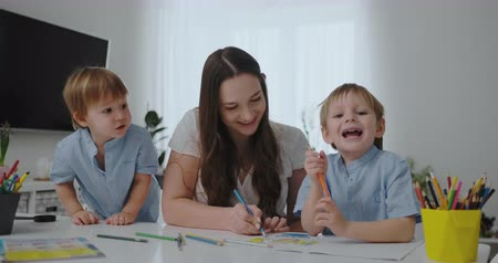 alfabetização : A young mother with two children sitting at a white table draws colored pencils on paper in slow motion Stock Footage