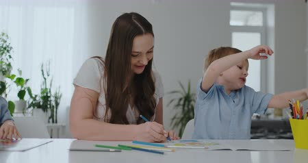 alfabetização : A family of two children and a young mother sitting at the table draws on paper with colored pencils. Development of creativity in children. Stock Footage