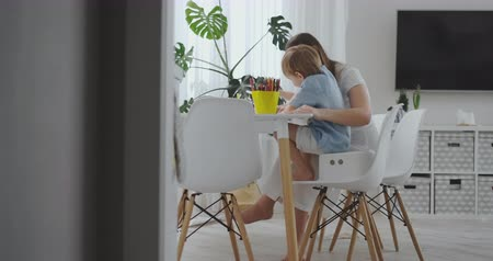 alfabetização : A young mother with two children sitting at a white table draws colored pencils on paper in slow motion Vídeos