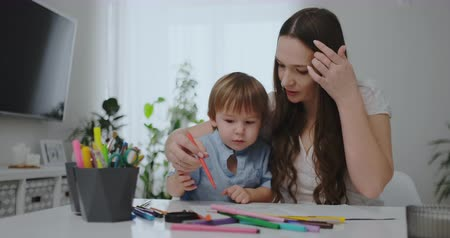 gramotnost : A family of two children and a young mother sitting at the table draws on paper with colored pencils. Development of creativity in children. white clean interior
