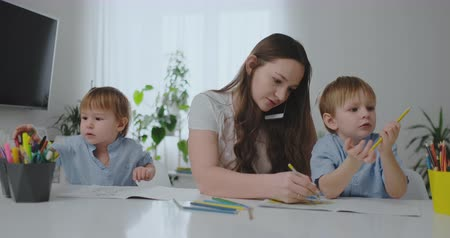 alfabetização : A young mother with two children talking on a mobile phone draws with a pencil and helps children draw with colored pencils Stock Footage