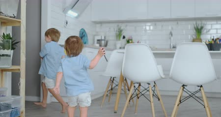 портфель : Two children jump and enjoy running in the house in the kitchen