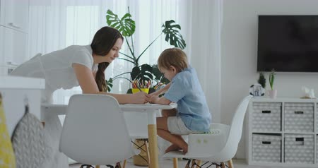 портфель : Two boy sitting on kitchen light draw pencils drawings for school-quests. Mom looks at the children and smiles in the kitchen