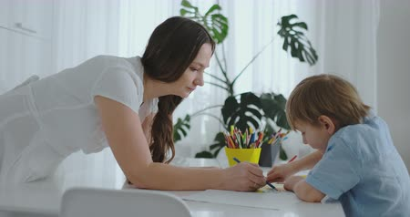 портфель : Mom helps son to perform preschool homework to draw a pencil drawing sitting at the table in the house