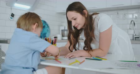 портфель : Young beautiful mom and son draw with colored pencils sitting at the table in the kitchen