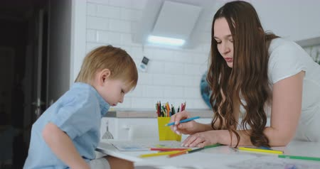 портфель : Mom helps sons learn to draw doing homework preschool preparation at home sitting in the white kitchen. Стоковые видеозаписи
