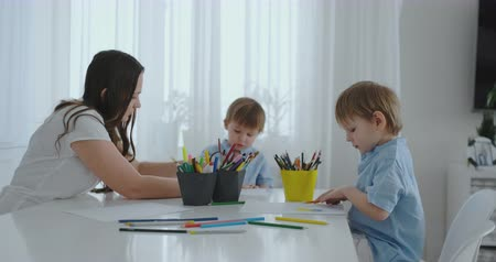 портфель : Mom helps two sons to perform preschool homework to draw a pencil drawing sitting at the table in the house