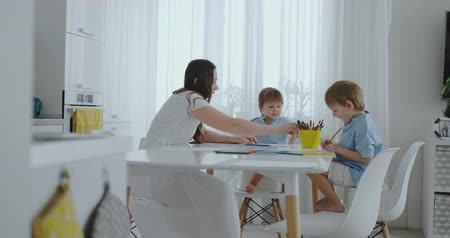 gramotnost : Mom helps sons learn to draw doing homework preschool preparation at home sitting in the white kitchen. Dostupné videozáznamy