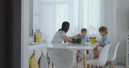 gramotnost : Mom helps sons learn to draw doing homework preschool preparation at home sitting in the white kitchen. Two brothers draw a portrait of mom together Dostupné videozáznamy