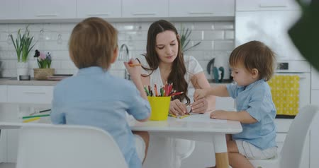 портфель : Two children of boys draw with his mother sitting in the kitchen. Happy family at home.